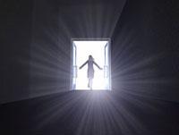 暗闇に開いたドアから駆け出す女性