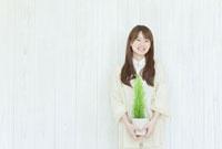 壁の前に立ち笑顔の若い日本人女性