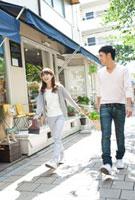 買い物をして歩く若い夫婦