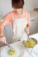 スパゲティを皿に盛りつけする女性