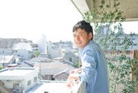 ベランダに立つ若い男性 10367000368| 写真素材・ストックフォト・画像・イラスト素材|アマナイメージズ