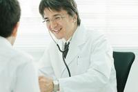 男性を診察する日本人の医師