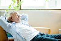 ソファーに寝転ぶシニア男性