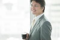 窓際に立ちコーヒーを飲む笑顔のビジネスマン
