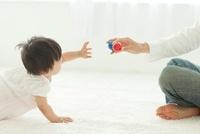 父親からボールを取ろうとする赤ちゃん
