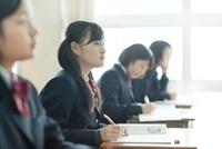 教室で真剣に授業を受ける女子校生