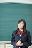 黒板の前に立ち考える女子校生