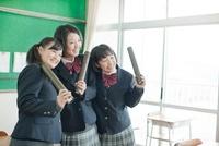 卒業証書を持つ笑顔の女子校生