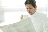 コーヒーカップを持ち新聞を読むシニア男性 10367003432| 写真素材・ストックフォト・画像・イラスト素材|アマナイメージズ