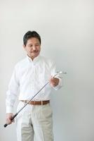壁の前に立ちゴルフクラブを持つシニア男性 10367003466| 写真素材・ストックフォト・画像・イラスト素材|アマナイメージズ