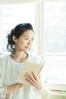 窓辺で本を読む若い女性