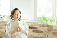 窓辺で本を読み目を閉じる若い女性