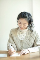 年賀状を書く若い女性 10367003766| 写真素材・ストックフォト・画像・イラスト素材|アマナイメージズ