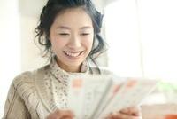 年賀状を読む若い女性 10367003768| 写真素材・ストックフォト・画像・イラスト素材|アマナイメージズ
