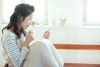 コーヒーを飲みながらスマートフォンを操作する若い女性