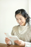 年賀状を読む若い女性
