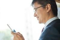 スマートフォンを操作するビジネスマン 10367003893| 写真素材・ストックフォト・画像・イラスト素材|アマナイメージズ