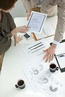 タブレットPCで打ち合せするビジネスマンとビジネスウーマン