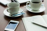 テーブルに置かれたスマートフォンとノートとコーヒー