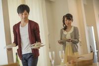 夕食の料理を運ぶ若いカップル