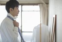 自宅でネクタイを結ぶフレッシュマン