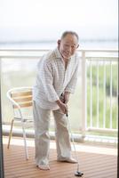 バルコニーでゴルフの練習をするシニア男性 10367005820| 写真素材・ストックフォト・画像・イラスト素材|アマナイメージズ