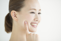頬に指をあてる女性のスキンケアイメージ
