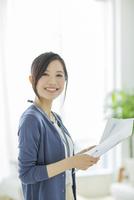 書類を持つ笑顔のビジネスウーマン 10367005994| 写真素材・ストックフォト・画像・イラスト素材|アマナイメージズ