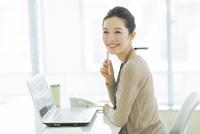 机に座る笑顔のビジネスウーマン 10367006036| 写真素材・ストックフォト・画像・イラスト素材|アマナイメージズ