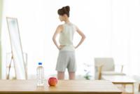 テーブルの上のリンゴと水と鏡を見る女性