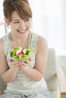 サラダを持って笑顔の若い女性