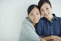 笑顔で寄り添う母親と娘
