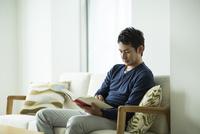 ソファーで読書をする男性