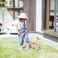 庭で遊ぶ女の子とウサギ