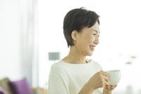 コーヒーカップを持った笑顔のシニア女性