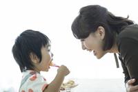 プリンを食べる男の子と見守る母親