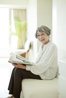 ソファーで雑誌を読むシニア女性