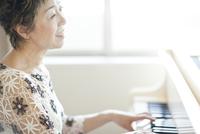 ピアノを弾き歌を歌う中高年女性