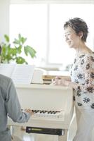 ピアノのレッスンをする中高年女性