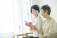 スマートフォンを持って笑顔の母と娘 10367007202| 写真素材・ストックフォト・画像・イラスト素材|アマナイメージズ