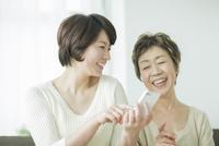 スマートフォンを持って笑顔の母と娘