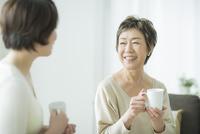 お茶を飲みながら笑顔で会話をする母娘