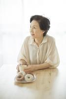 テーブルで考えるシニア女性 10367007479| 写真素材・ストックフォト・画像・イラスト素材|アマナイメージズ