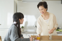 テーブルで勉強する孫と会話をする祖母