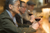 バーでワインを飲むシニア男性