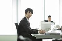 オフィスデスクに座る日本人ビジネスマン