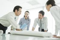 テーブルに図面を広げて打ち合わせをするビジネスマンとビジネスウーマン
