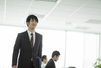 オフィスを歩くビジネスマン 10367008110| 写真素材・ストックフォト・画像・イラスト素材|アマナイメージズ