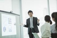 プロジェクターを使用した会議で説明をするビジネスマン