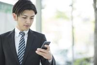 携帯電話を見るビジネスマン